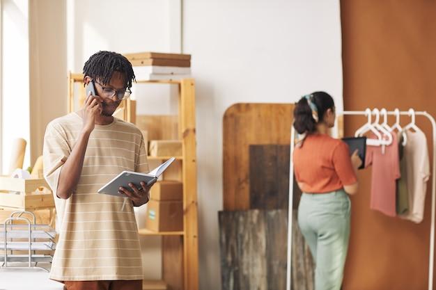 Młody afrykański mężczyzna rozmawia przez telefon i pracuje online na komputerze typu tablet on przyjmuje zamówienie z kobietą pracującą z ubraniami w tle