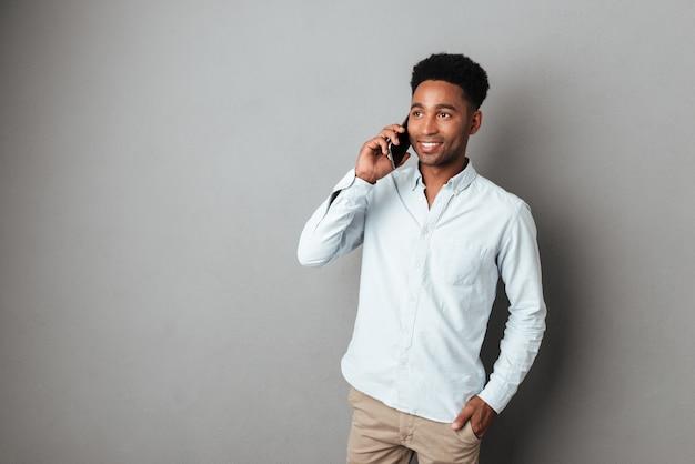 Młody afrykański mężczyzna rozmawia przez telefon komórkowy stojąc