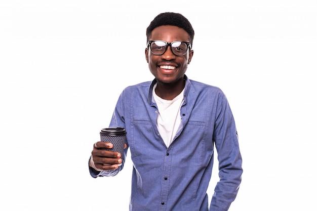 Młody afrykański mężczyzna trzyma filiżankę odizolowywająca na biel ścianie