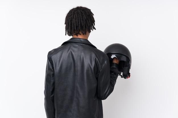 Młody afrykański mężczyzna trzyma motorowego hełm nad ścianą