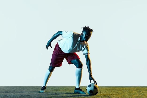 Młody afrykański mężczyzna w piłce nożnej lub w piłce nożnej w odzieży sportowej i butach kopiących piłkę