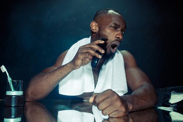 Młody afrykański mężczyzna w sypialni, siedząc przed lustrem, drapiąc się po brodzie w domu. koncepcja ludzkich emocji