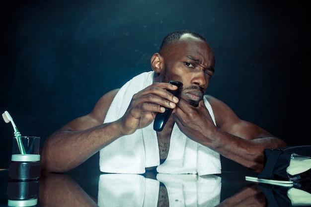 Młody afrykański mężczyzna w sypialni, siedząc przed lustrem, drapiąc się po brodzie w domu