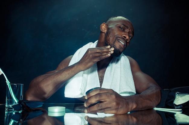 Młody afrykański mężczyzna w sypialni, siedząc przed lustrem po drapaniu brody w domu.