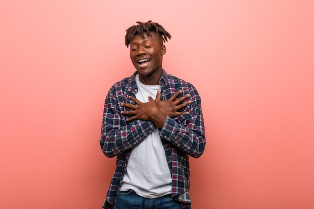 Młody afrykański murzyn śmiejąc się, trzymając ręce na sercu, pojęcie szczęścia.