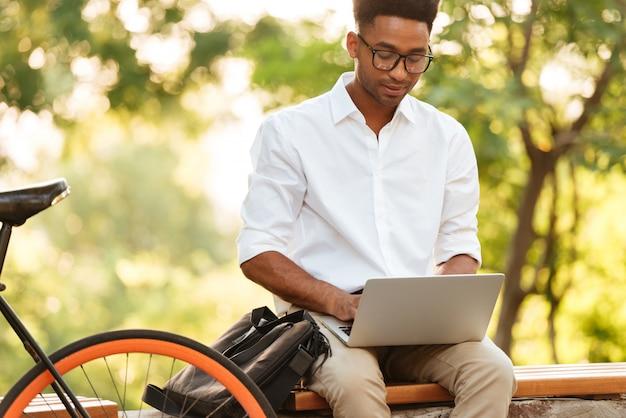 Młody afrykański przystojny mężczyzna używa laptop.