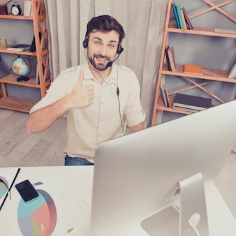Młody agent call center pokazuje kciuk do góry