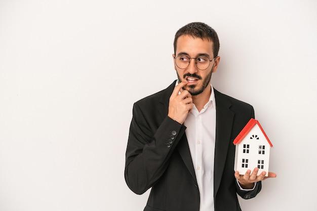 Młody agent nieruchomości mężczyzna posiadający model domu na białym tle zrelaksowany myślenie o czymś patrząc na miejsce na kopię.