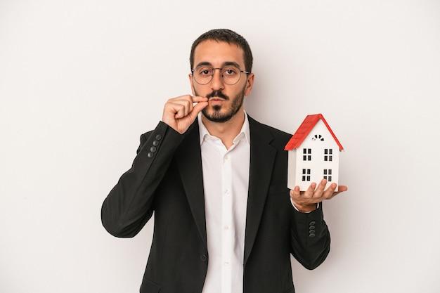 Młody agent nieruchomości mężczyzna trzyma model domu na białym tle z palcami na ustach zachowując tajemnicę.