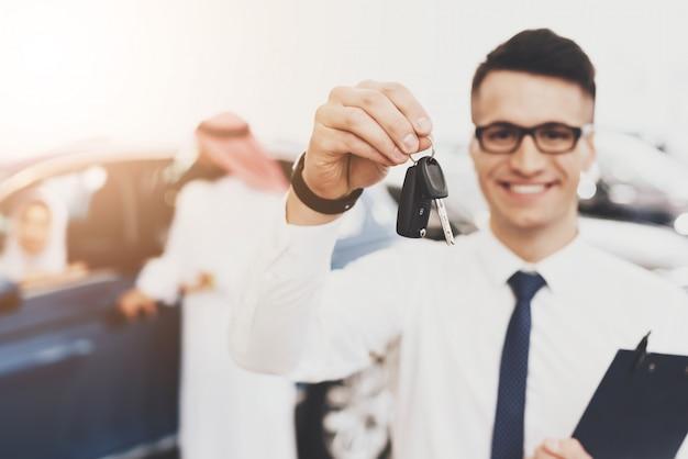 Młody agent w okularach trzyma samochód kluczyki auto salon
