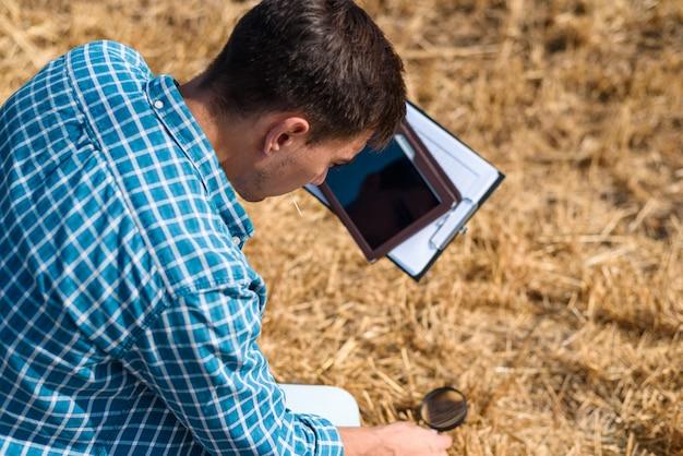 Młody agronom botanik studiuje skoszone siano z lupą i tabletem w polu