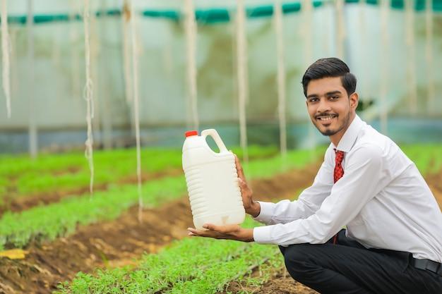 Młody agronom trzymając w ręku butelkę w szklarni