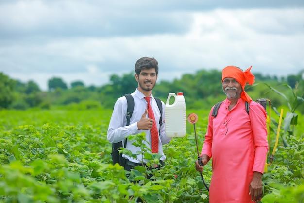 Młody agronom z rolnikiem pokazujący butelkę nawozu w polu