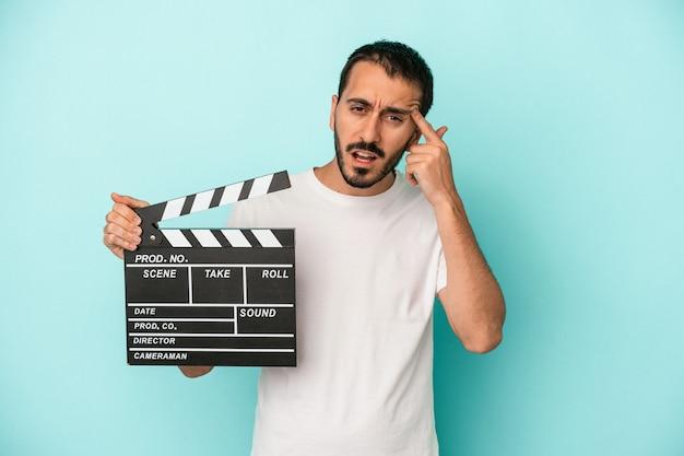 Młody aktor kaukaski mężczyzna trzyma klaps na białym tle na niebieskim tle pokazując gest rozczarowania palcem wskazującym.