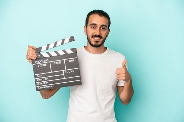 Młody aktor kaukaski mężczyzna trzyma klapsę na białym tle na niebieskim tle, uśmiechając się i podnosząc kciuk do góry