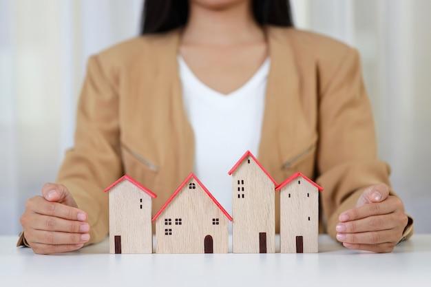 Młody aktywny biznes kobieta ręce w dorywczo sukienka siedzi i chroni model domu na białym stole.