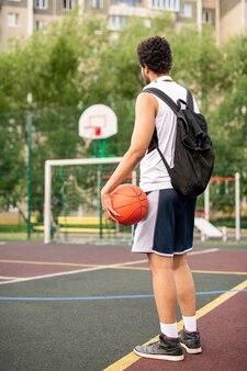 Młody aktywny koszykarz mężczyzna z piłką i plecakiem stojący przy białej linii na placu zabaw