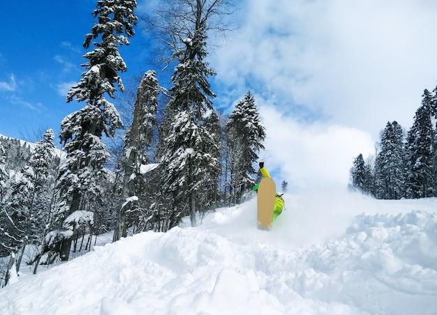 Młody aktywny zawodnik wolny na snowboardzie w puszystym śniegu