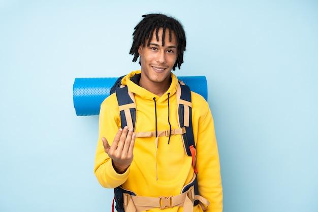 Młody alpinista afroamerykanin mężczyzna z dużym plecakiem odizolowywającym na błękitnej ścianie zaprasza przyjeżdżać