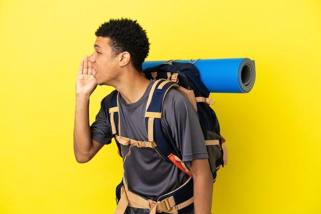 Młody alpinista afroamerykanin z dużym plecakiem na żółtym tle krzyczy z szeroko otwartymi ustami