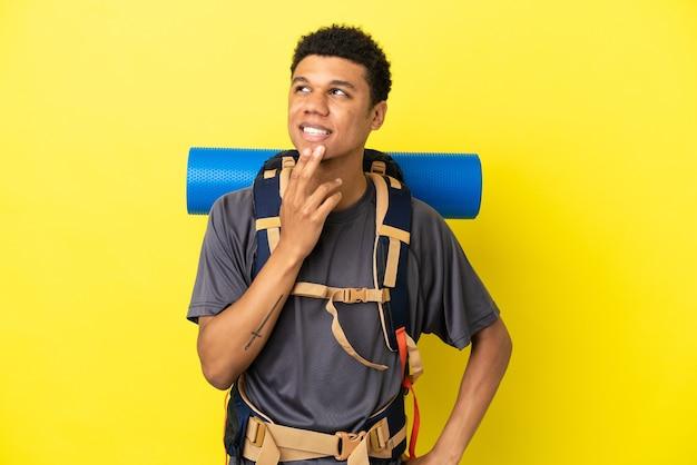 Młody alpinista afroamerykanin z dużym plecakiem na żółtym tle, patrząc w górę, uśmiechając się