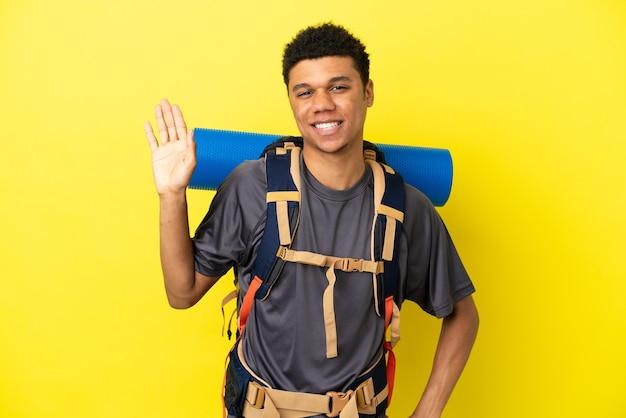 Młody alpinista afroamerykanin z dużym plecakiem na żółtym tle pozdrawiający ręką ze szczęśliwym wyrazem twarzy