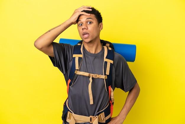 Młody alpinista afroamerykanin z dużym plecakiem na żółtym tle robi gest zaskoczenia, patrząc w bok