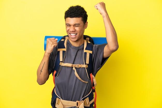 Młody alpinista afroamerykanin z dużym plecakiem na żółtym tle świętujący zwycięstwo