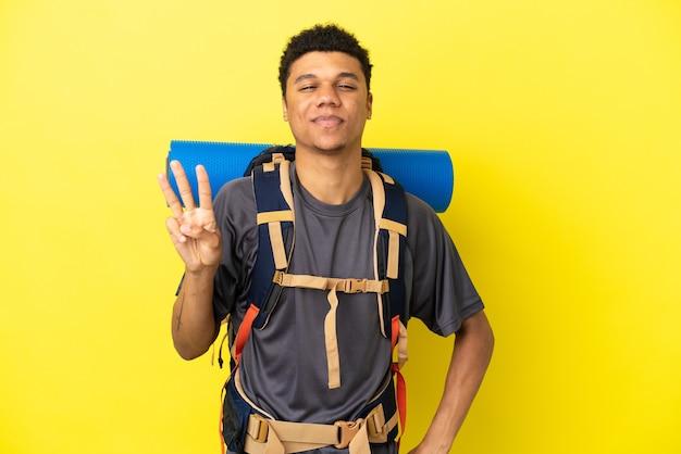 Młody alpinista afroamerykanin z dużym plecakiem na żółtym tle szczęśliwy i liczący trzy palcami