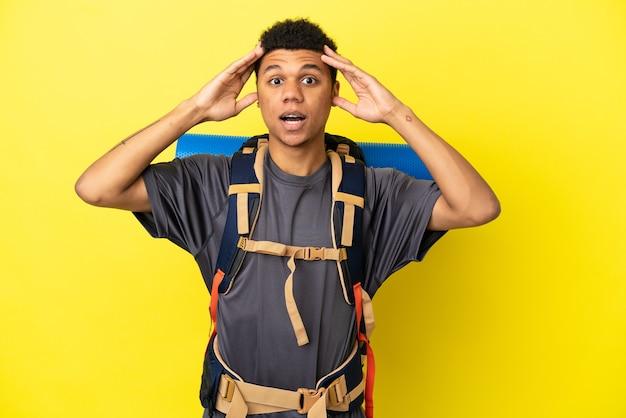 Młody alpinista afroamerykanin z dużym plecakiem na żółtym tle z wyrazem zaskoczenia
