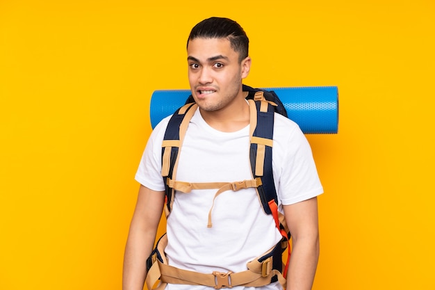 Młody alpinista azjatycki człowiek z dużym plecakiem na białym tle na żółtym tle, mający wątpliwości iz niejasnym wyrazem twarzy