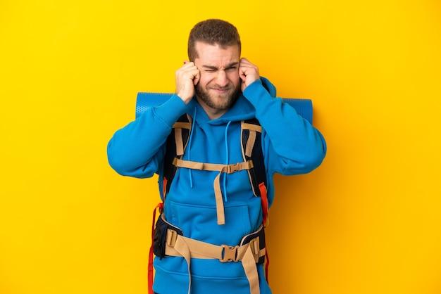 Młody alpinista kaukaski mężczyzna z dużym plecakiem na białym tle na żółte uszy sfrustrowane i stożkowate