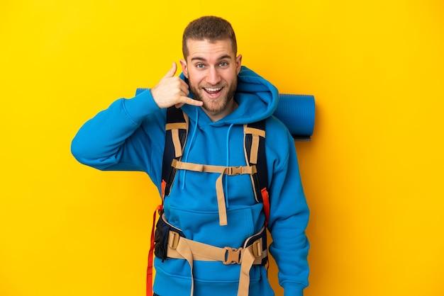 Młody alpinista kaukaski mężczyzna z dużym plecakiem na białym tle na żółtej ścianie, czyniąc gest telefonu. oddzwoń do mnie znak