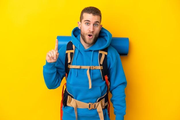 Młody alpinista kaukaski mężczyzna z dużym plecakiem na białym tle na żółtej ścianie myśli pomysł, wskazując palcem w górę