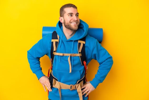 Młody alpinista kaukaski mężczyzna z dużym plecakiem na białym tle na żółtej ścianie, pozowanie z rękami na biodrze i uśmiechnięty