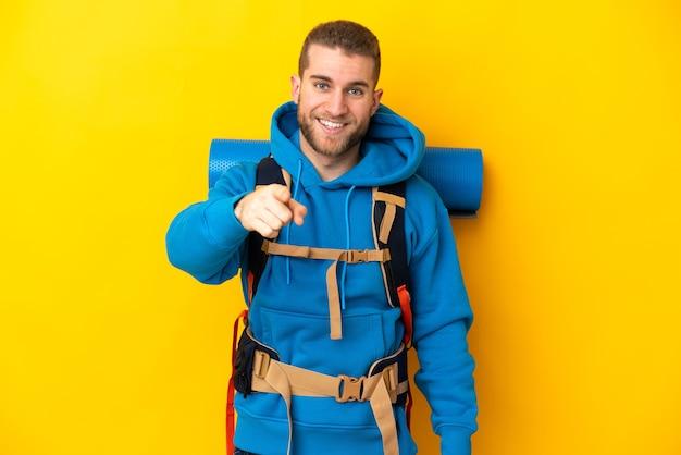 Młody alpinista kaukaski mężczyzna z dużym plecakiem na białym tle na żółtej ścianie zaskoczony i wskazujący przód