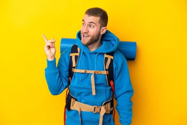 Młody alpinista kaukaski mężczyzna z dużym plecakiem na żółtej ścianie z zamiarem znalezienia rozwiązania, podnosząc palec w górę