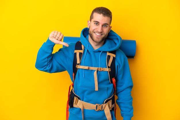Młody alpinista kaukaski mężczyzna z dużym plecakiem na żółtym tle dumny i zadowolony z siebie