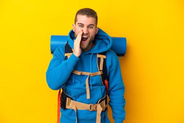 Młody alpinista kaukaski mężczyzna z dużym plecakiem na żółtym tle, krzycząc z szeroko otwartymi ustami