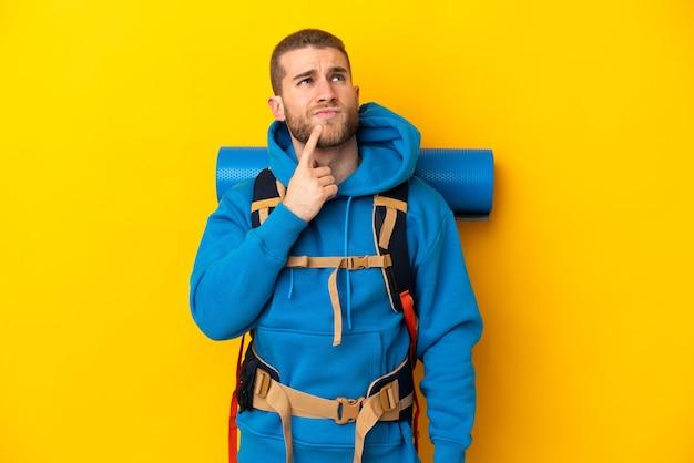 Młody alpinista kaukaski mężczyzna z dużym plecakiem na żółtym tle, mając wątpliwości podczas patrzenia w górę