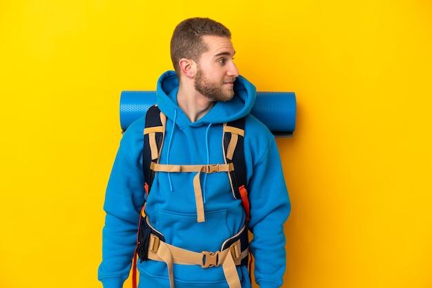 Młody alpinista kaukaski mężczyzna z dużym plecakiem na żółtym tle patrząc z boku