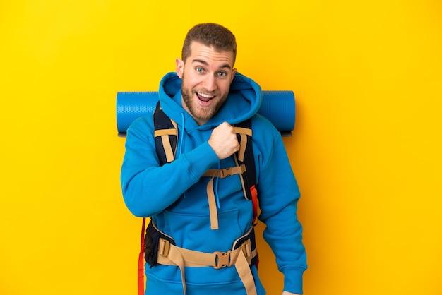 Młody alpinista kaukaski mężczyzna z dużym plecakiem na żółtym tle świętuje zwycięstwo