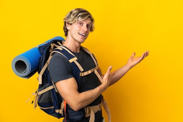 Młody alpinista mężczyzna nad odosobnioną żółtą ścianą wyciągając ręce na bok za zaproszenie do przybycia