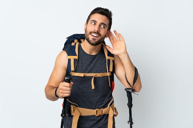 Młody alpinista mężczyzna z dużym plecakiem i trekkingowymi kijami odizolowywającymi na biel ścianie słucha coś
