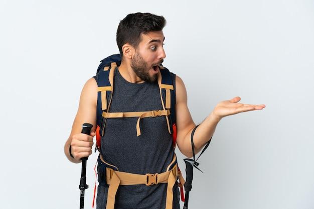 Młody alpinista mężczyzna z dużym plecakiem i trekkingowymi kijami odizolowywającymi na biel ścianie trzyma copyspace imaginacyjnego na dłoni