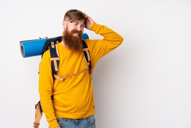 Młody alpinista mężczyzna z dużym plecakiem nad odosobnioną biel ścianą ma wątpliwości i z zmieszanym wyrazem twarzy