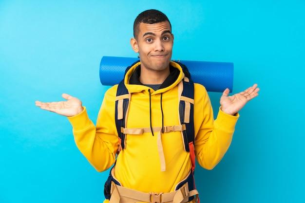 Młody alpinista mężczyzna z dużym plecakiem nad odosobnioną błękit ścianą ma wątpliwości z zmieszanym wyrazem twarzy