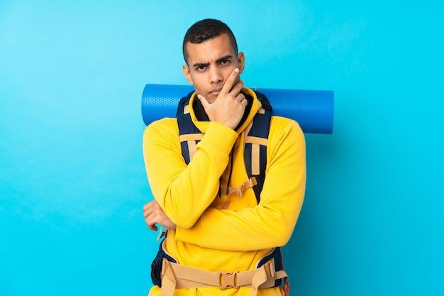 Młody alpinista mężczyzna z dużym plecakiem nad odosobnioną błękit ścianą myśleć pomysł