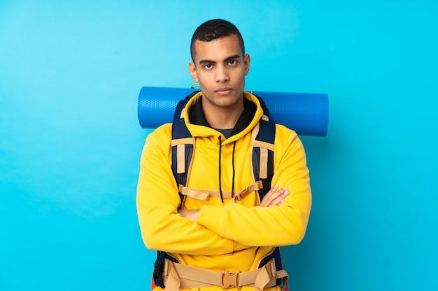Młody alpinista mężczyzna z dużym plecakiem nad odosobnioną błękit ścianą utrzymuje ręki krzyżować