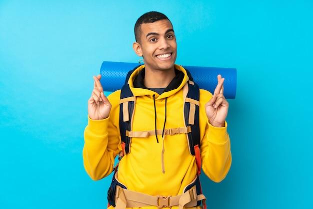 Młody alpinista mężczyzna z dużym plecakiem nad odosobnioną błękit ścianą z palców krzyżować